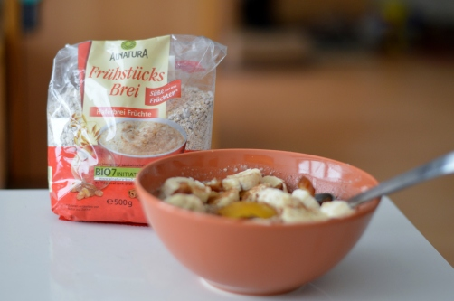 warmer Frühstücksbrei von Alnatura mit Mandelmilch, einer Banane, einem Pfirsich, Erdnussmus (crunchy), Datteln, Kakao, Zimt und Vanille